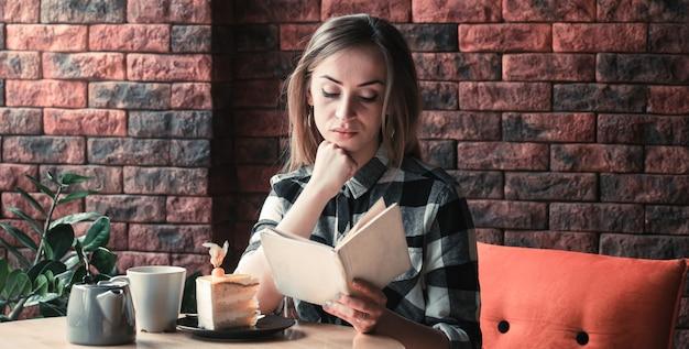 Schönes mädchen liest ein buch in einem café Kostenlose Fotos