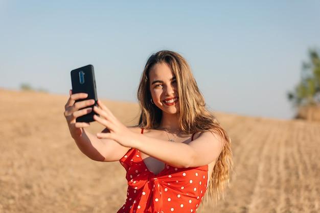 Schönes mädchen macht ein selfie im freien in einem sommersonnenuntergang Premium Fotos