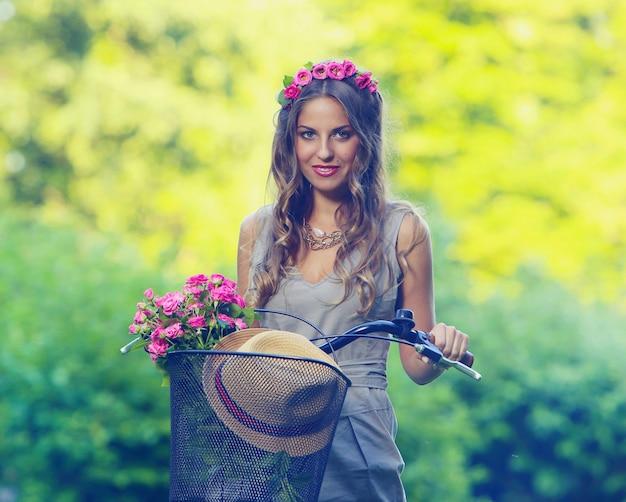 Schönes mädchen mit blumen auf einem fahrrad Kostenlose Fotos