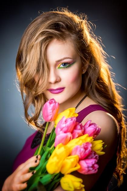 Schönes mädchen mit blumentulpen Premium Fotos