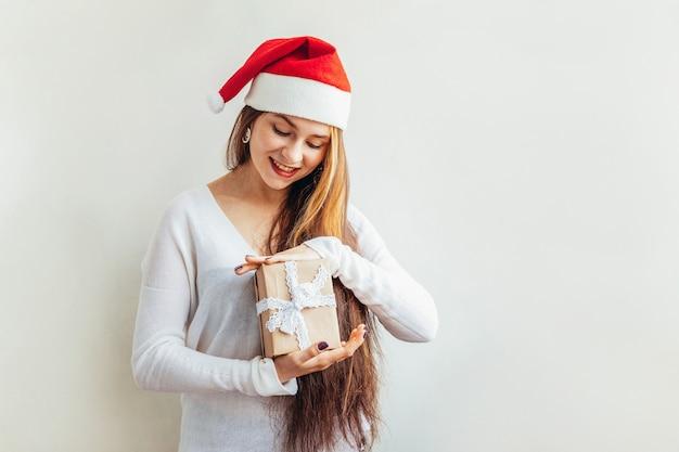 Schönes mädchen mit dem langen haar in rotem santa claus-hut, der geschenkbox lokalisiert auf dem weiß schaut glücklich und aufgeregt hält. Premium Fotos