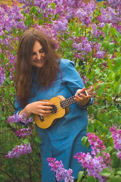 Schönes mädchen mit dem lockigen haar kleidete im denimkleid an, welches die ukulele spielt Premium Fotos