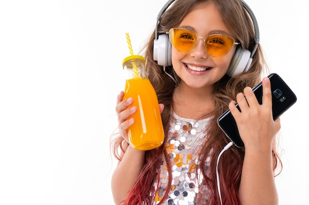Schönes mädchen mit den großen weißen kopfhörern, die schwarzen smartphone und flasche mit orangensaft halten Premium Fotos