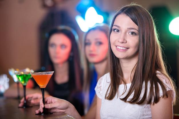 Schönes mädchen mit einem cocktail in ihrem handlächeln. Premium Fotos