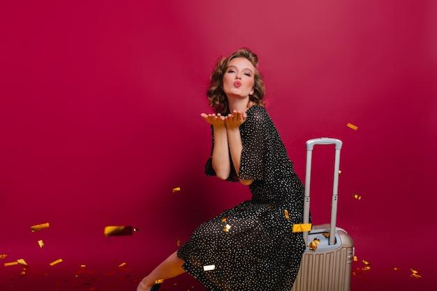 Schönes mädchen mit kurzer eleganter frisur sendet luftküsse, während auf koffer sitzend Kostenlose Fotos