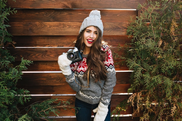 Schönes mädchen mit langen haaren in strickmütze und weißen handschuhen auf grünen zweigen der hölzernen einfassung. sie trägt einen warmen pullover, hält die kamera und sieht gut aus. Kostenlose Fotos