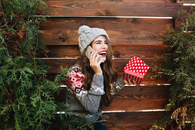 Schönes mädchen mit langen haaren mit weihnachtskiste auf grünen zweigen der hölzernen einfassung. sie trägt warme winterkleidung, telefoniert und lacht zur seite. Kostenlose Fotos