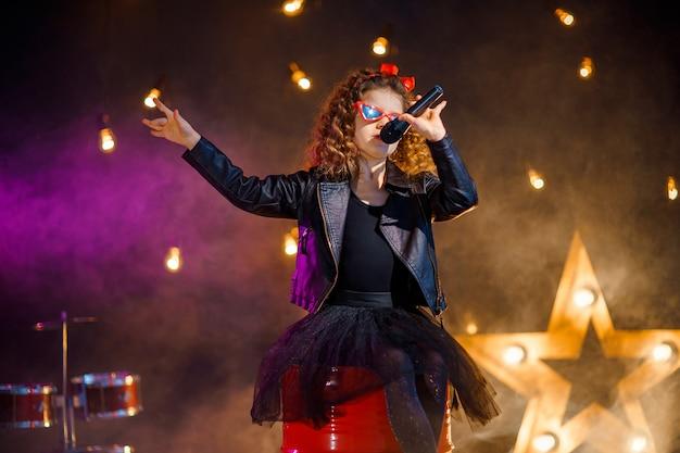 Schönes mädchen mit lockigem haar, das lederjacke und rote sonnenbrille trägt, singt in ein drahtloses mikrofon für karaoke im aufnahmestudio Premium Fotos