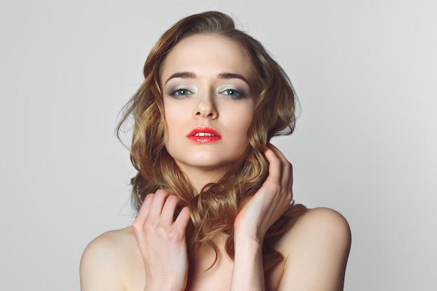 Schönes mädchen mit lockigem haar, hellem und luftigem make-up, rosa lippen. Premium Fotos