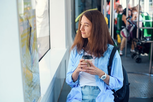 Schönes mädchen mit tasse köstlichen kaffee fährt zur universität im öffentlichen verkehr. Premium Fotos