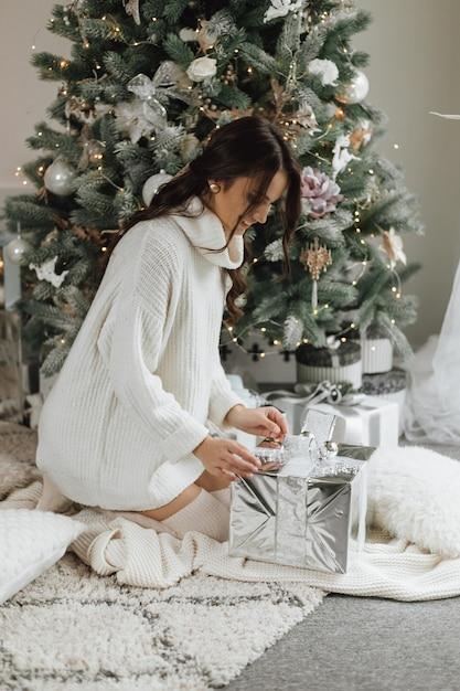 Schönes mädchen sieht sehr glücklich aus und packt ein geschenk auf einem weihnachtsbaumhintergrund aus Kostenlose Fotos