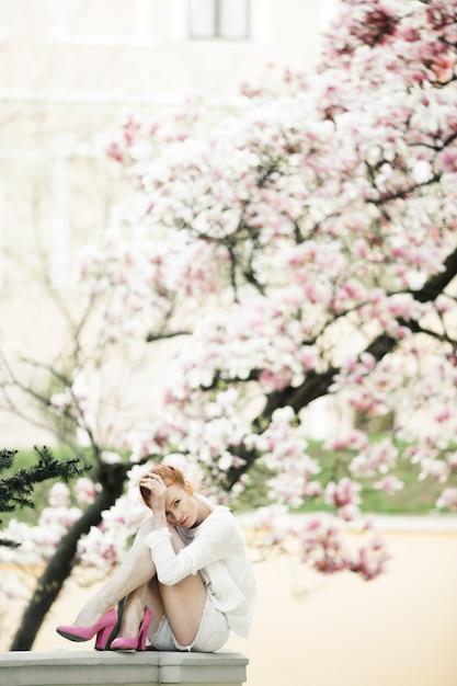 Schönes mädchen sitzt am geländer nahe dem erstaunlichen magnolienbaum Kostenlose Fotos