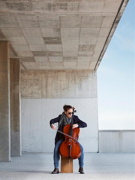 Schönes mädchen spielt das cello mit leidenschaft in einer konkreten umgebung Kostenlose Fotos
