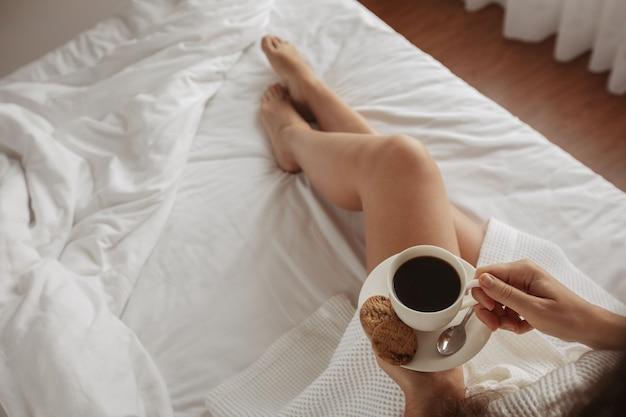 Schönes mädchen trinkt kaffee mit plätzchenbett Premium Fotos