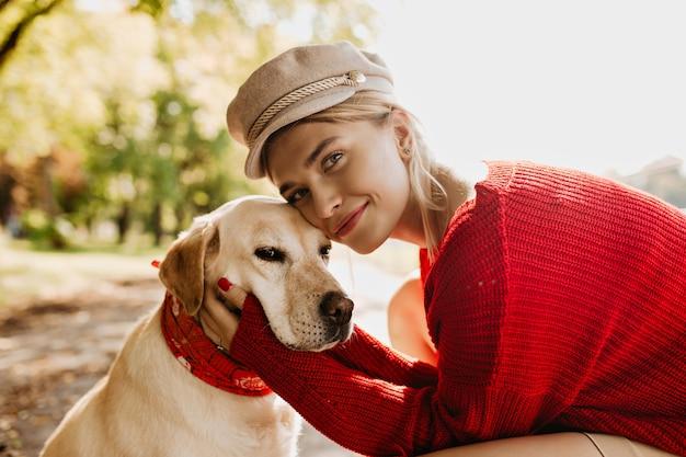 Schönes mädchen und ihr hund zusammen mit liebe. charmante blonde frau mit ihrem haustier, das sonnigen herbsttag genießt. Kostenlose Fotos