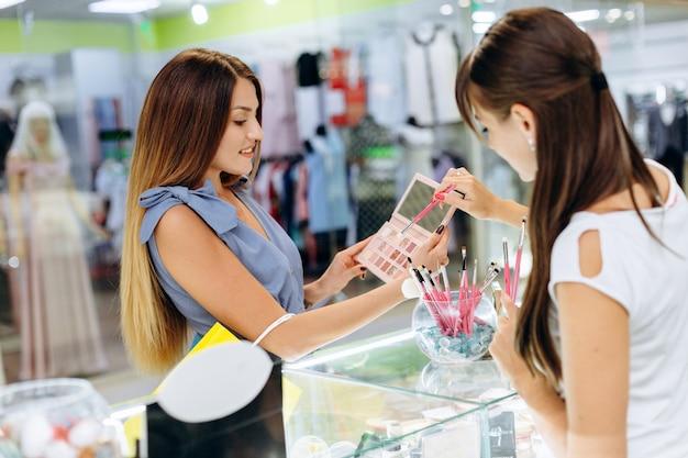 Schönes mädchen wählt kosmetik im mall. Premium Fotos