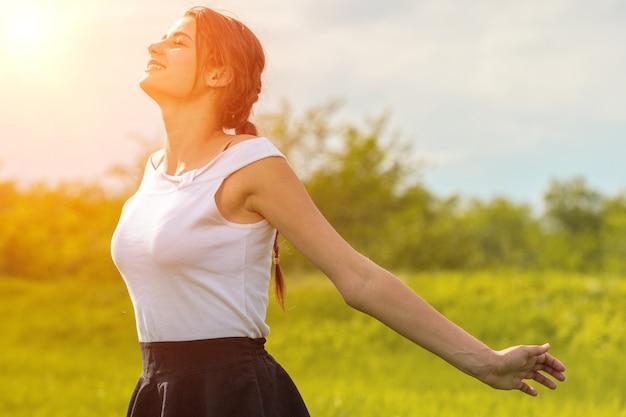 Schönes mädchen, welches die sonne mit ihren armen genießt, streckte auf dem gebiet gegen den himmel aus Premium Fotos