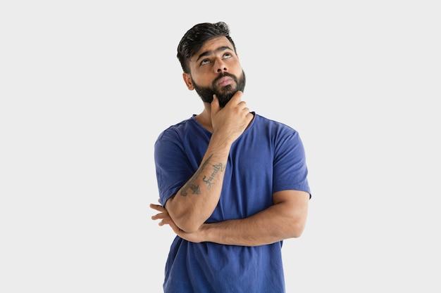 Schönes männliches halbes längenporträt lokalisiert auf weißem studiohintergrund. junger emotionaler hinduistischer mann im blauen hemd. gesichtsausdruck, menschliche emotionen, werbekonzept. denken oder wählen. Kostenlose Fotos