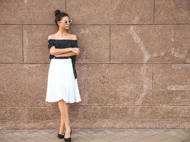 Schönes modell kleidete in der eleganten sommerkleidung an sexy sorgloses mädchen, das in der straße nahe wand aufwirft trendy moderne geschäftsfrau in der sonnenbrille, die spaß hat Kostenlose Fotos