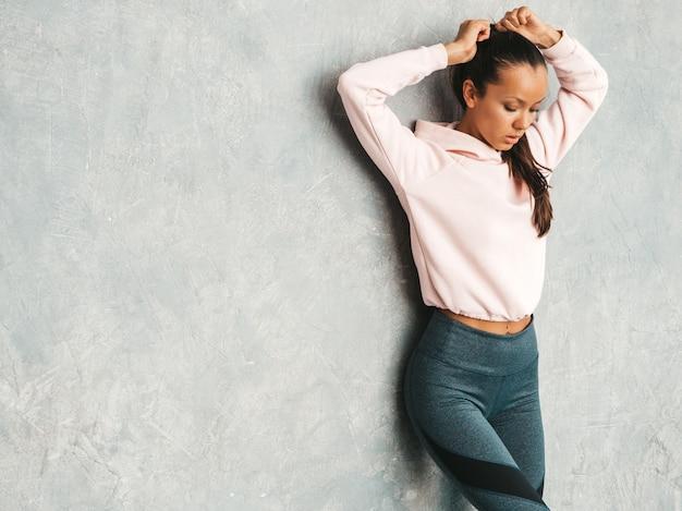 Schönes modell mit perfektem gebräuntem körper frau, die im studio nahe grauer wand aufwirft Kostenlose Fotos