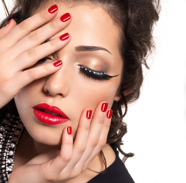 Schönes modell mit roten nägeln, lippen und kreativem augenmake-up - lokalisiert auf weißer wand Kostenlose Fotos