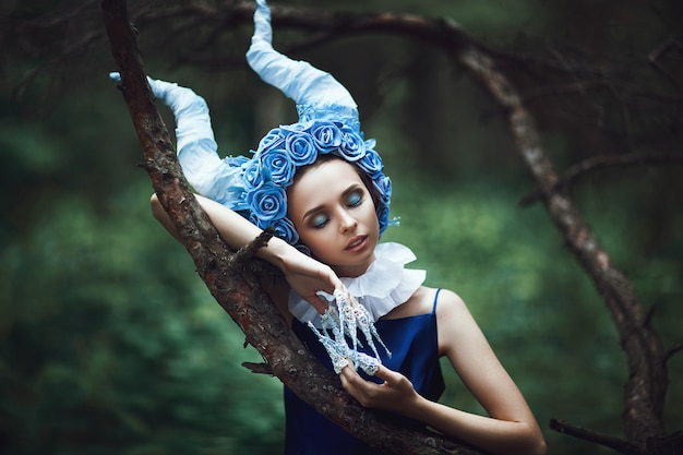 Schönes modell posiert in einem wald mit blauen hörnern Premium Fotos