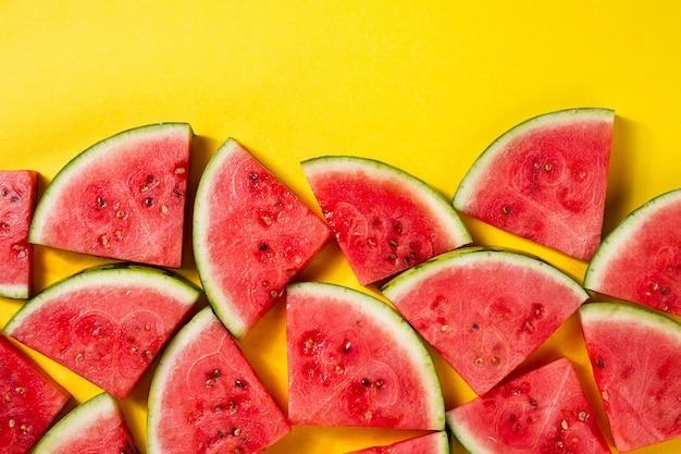 Schönes muster mit frischen wassermelone scheiben auf gelb hellen hintergrund. draufsicht. text kopieren Kostenlose Fotos