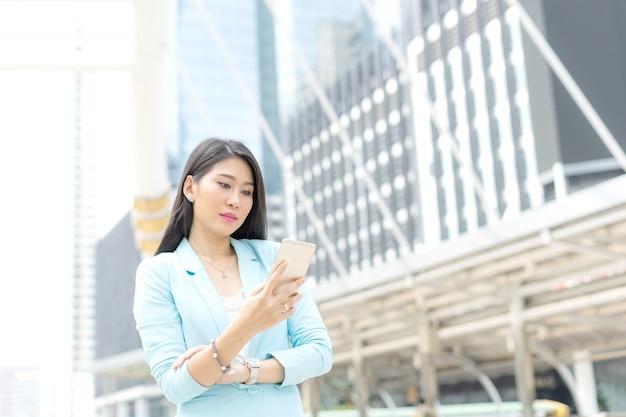 Schönes nettes mädchen in der geschäftsfrau kleidet unter verwendung des intelligenten telefoncomputergeschäfts concep Premium Fotos