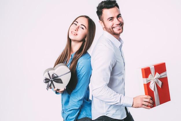 Schönes paar, das geschenke hält und kamera betrachtet Premium Fotos