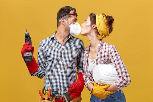 Schönes paar, das reparatur ihres hauses tut, das zusammen arbeitet und minute der entspannung hat, die leidenschaftlich küsst. junger baumeister männlich in der maske mit bohrmaschine, die mit liebe seine freundin ansieht Kostenlose Fotos