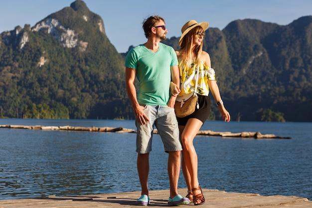 Schönes paar, das zusammen den pier vor dem erstaunlichen blick auf berge, reisestimmung, stilvolle sommerkleidung und accessoires aufwirft. khao sok thailand nationalpark. Kostenlose Fotos