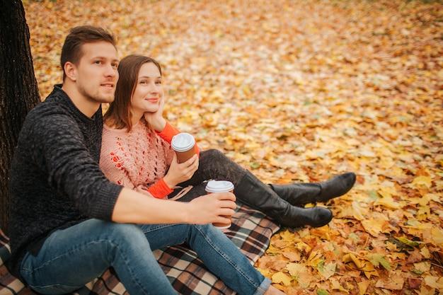 Schönes paar, das zusammen sitzt und in eine richtung schaut. sie halten tassen kaffee. er umarmt sie. sie sitzen im park. Premium Fotos
