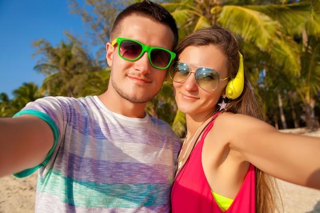 Schönes paar des jungen hipsters verliebt in selfie-foto am tropischen strand, sommerferien, glücklich zusammen, flitterwochen, bunter stil, sonnenbrille, kopfhörer, lächelnd, glücklich, spaß haben, positiv Kostenlose Fotos