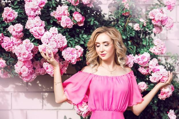 Schönes porträt blondine in den rosa rosen. nahaufnahme, make-up, verlängerte wimpern Premium Fotos