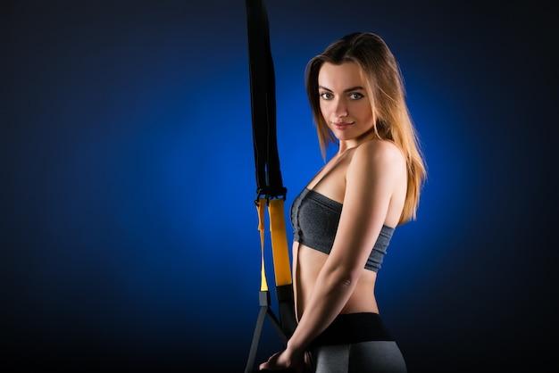 Schönes positives junges mädchen-fitnessmodell, das im studio posiert, das an hängenden trägern festhält Premium Fotos