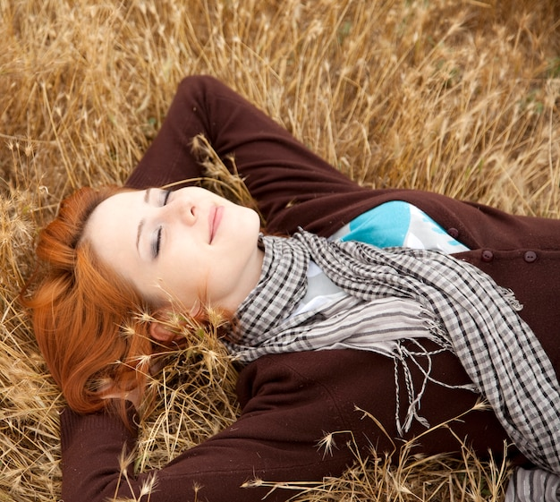 Schönes rothaarigemädchen, das sich auf gelbem gras hinlegt. herbstzeit Premium Fotos