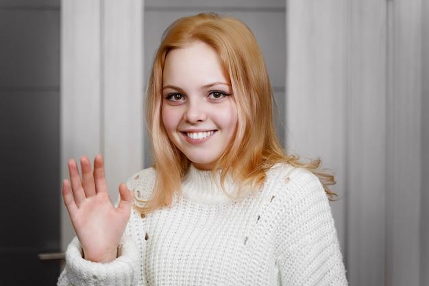 Schönes rothaariges mädchen winkt schüchtern mit der hand