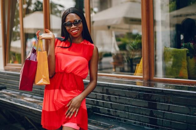 Schönes schwarzes mädchen mit einkaufstüten in einer stadt Kostenlose Fotos