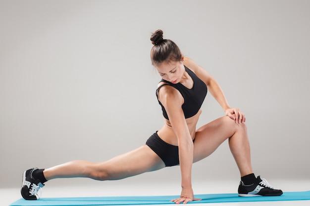 Schönes sportliches mädchen, das in der akrobatenhaltung oder in der yoga asana steht Kostenlose Fotos