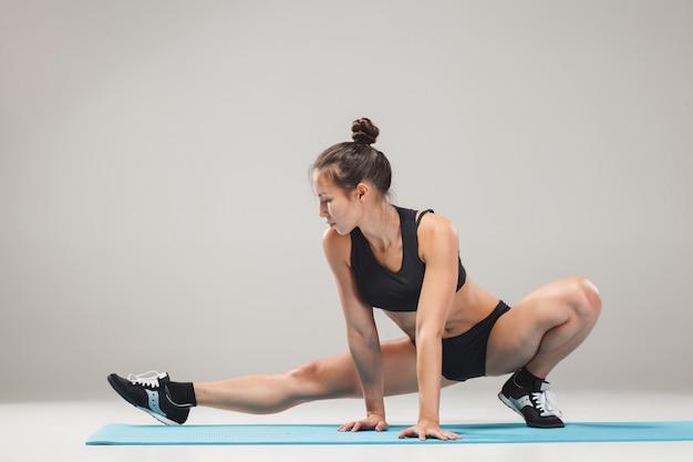Schönes sportliches mädchen, das in der akrobatenhaltung steht Kostenlose Fotos