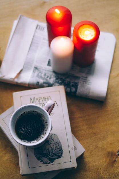 Schönes stillleben von büchern, kerzen und schwarzem kaffee auf dem tisch Premium Fotos