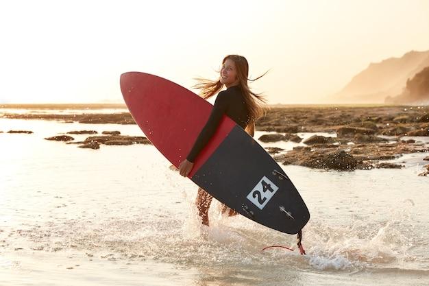 Schönes surfmädchen hat aktiven lebensstil, trägt surfbrett, sieht glücklich aus Kostenlose Fotos