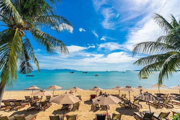 Schönes tropisches strandmeer und -ozean mit kokosnusspalme und regenschirm und stuhl auf blauem himmel Kostenlose Fotos
