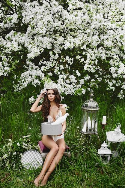 Schönes und sexy modell mit perfektem körper in stilvollen dessous mit der krone auf ihrem kopf, die mit den tauben unter dem blühenden baum am grünen wald aufwirft Premium Fotos