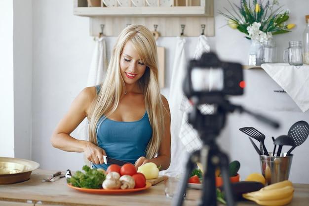 Schönes und sportliches mädchen in einer küche, die ein video notiert Kostenlose Fotos