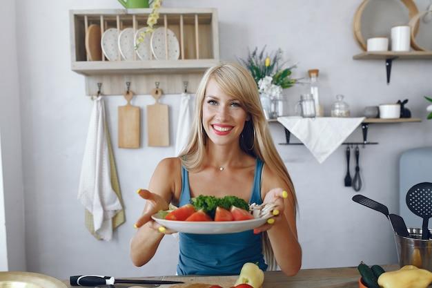 Schönes und sportliches mädchen in einer küche mit gemüse Kostenlose Fotos
