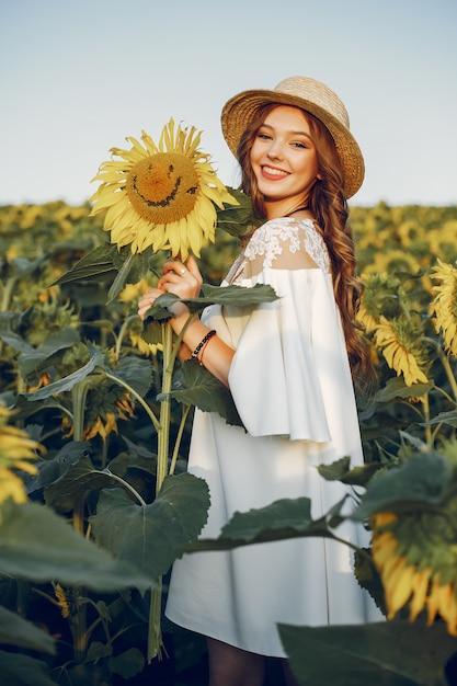 Schönes und stilvolles mädchen auf einem gebiet mit sonnenblumen Kostenlose Fotos