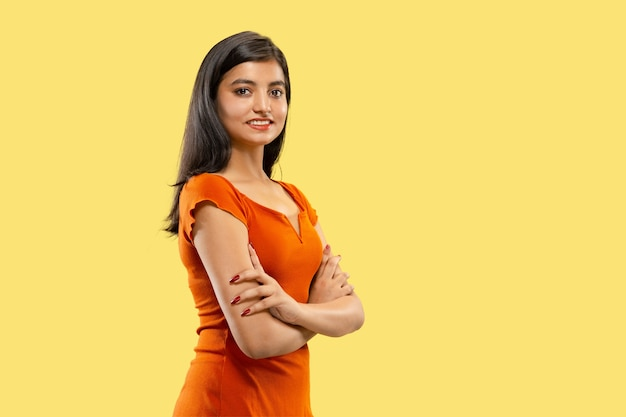 Schönes weibliches halbes längenporträt lokalisiert. junge emotionale indische frau im kleid stehend, das hände kreuzt. negativer raum. gesichtsausdruck, menschliches gefühlskonzept. Kostenlose Fotos