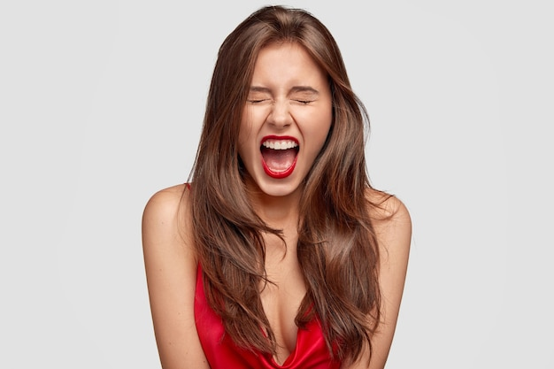 Schönes weibliches model ruft wütend aus, ist emotional, hat rote lippen, gesunde reine haut, zeigt nackte schultern, isoliert über weißer wand. menschen, stil, make-up, emotionen konzept Kostenlose Fotos