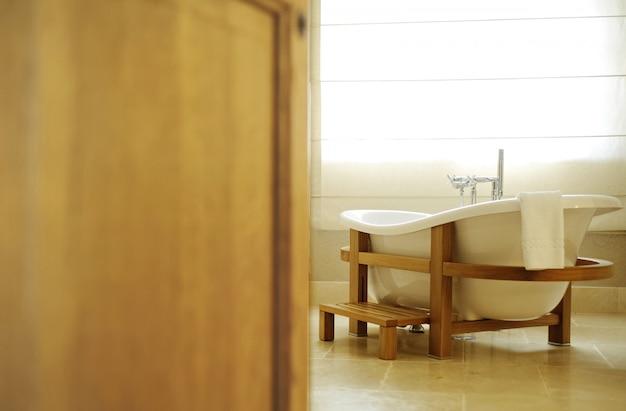 Schönes weißes bad für eine offene tür. bad steht in einem hölzernen f Premium Fotos